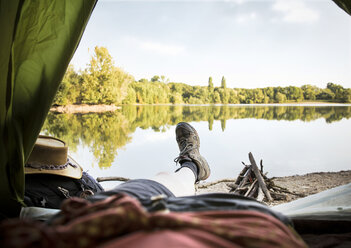 Legs of a woman lying in tent at a lake - ONF01074