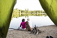 Senior couple camping with dog at a lake - ONF01077