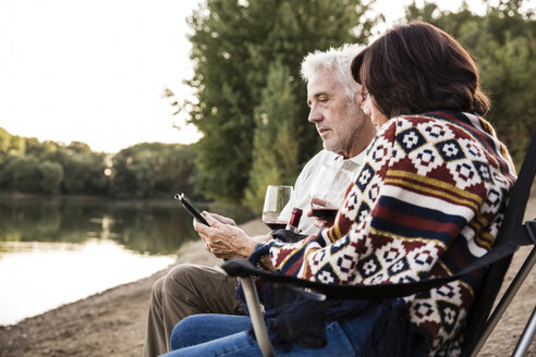 Senior couple with wine sitting at a lake with tablet - ONF01083