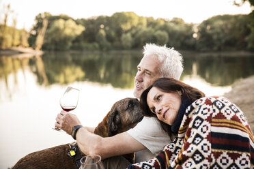Relaxed senior couple with dog and wine at a lake - ONF01086