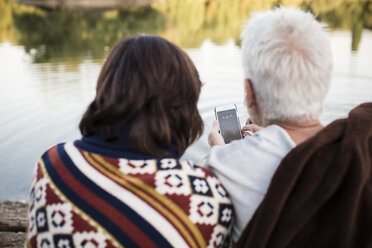 Senior couple with cell phone at a lake - ONF01089