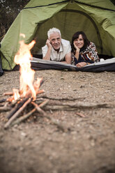 Happy senior couple lying in tent at campfire - ONF01101