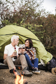 Senior couple sitting at campfire with wine in a tent - ONF01104