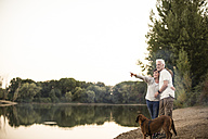 Senior couple with dog at a lake - ONF01110
