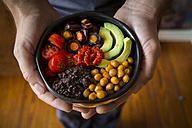Man's hands holding Buddha bowl of amaranth, avocado, Purple Haze, roasted chickpeas, tomatoes, ajvar - LVF05388