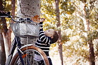 Toddler taking autumn leaf from bike - JPSF00021