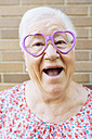 Portrait of happy senior woman wearing heart-shaped glasses pulling funny faces - GEMF01121