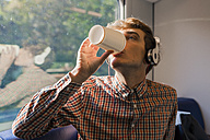 Young man with headphones drinking coffee to go in a train - FMOF00126