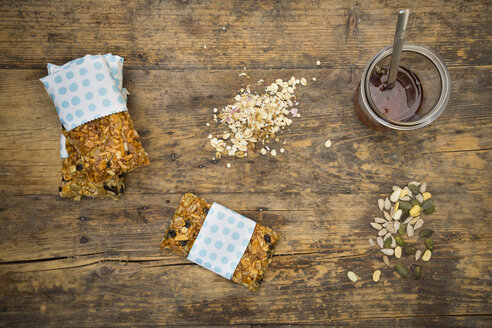 Homemade granola bars and a glass of honey on wood - LVF05402