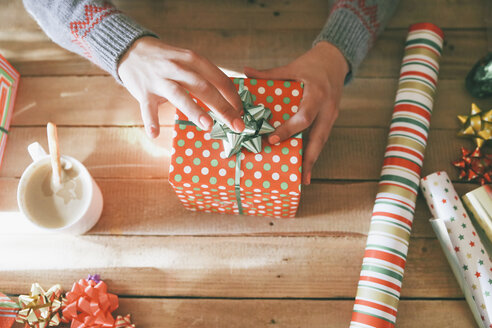 Woman's hands placing tie on Christmas gift - RTBF00427