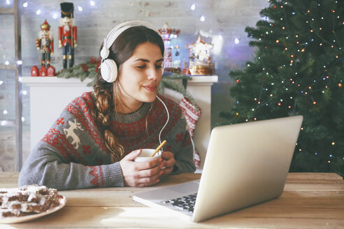 Woman with cup of coffee using laptop and headphones at Christmas time - RTBF00430