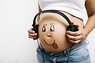 Pregnant woman holding headphones at her painted belly - JRFF00909