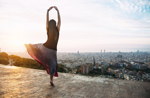 Spain, Barcelona, Woman ldancing at view point over city - GEMF01130