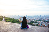 Spain, Barcelona, Woman taking picture of thhe city with her smart phone - GEMF01133