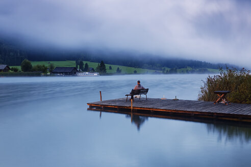 Austria, Carinthia, Man sitting on jetty at Lake Weissensee - GFF00784
