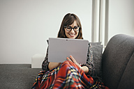 Young woman covered with blanket relaxing on the couch with her tablet - LCUF00043