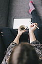 Top view of young woman sitting on the couch with tablet and cup of coffee holding stylus - LCUF00049