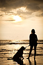 Mexico, Nayarit, silhouette of young woman with her dog on a leash at a beach at sunset - ABAF02079