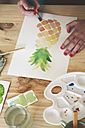 Woman's hand painting aquarelle of a pineapple at desk in her studio - RTBF00438