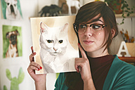 Portrait of artist showing aquarelle of a cat - RTBF00444
