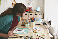 Artist watching French bulldog in her studio - RTBF00447