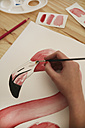 Woman's hand painting aquarelle of a flamingo on desk in her studio - RTBF00453