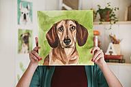 Artist hiding behind aquarelle of a dachshund - RTBF00459