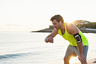 Spain, Mallorca, Jogger at the beach with headphones, looking on smartwatch - DIGF01363