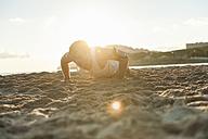Spain, Mallorca, Jogger at the beach at sunrise, pushups - DIGF01372