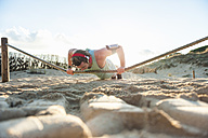 Spain, Mallorca, Jogger at the beach, pushups on rope - DIGF01381