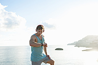 Spain, Mallorca, Jogger looking on smartwatch - DIGF01384