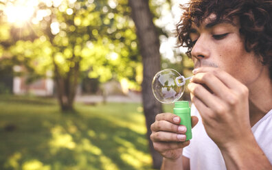 Young man blowing soap bubbles in park - DAPF00388