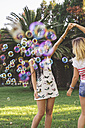 Female friends having fun with soap bubbles in park - DAPF00391