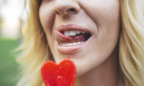 Close-up of young woman licking heart-shaped lollipop - DAPF00400