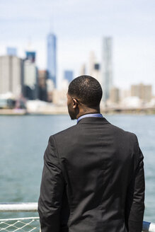 USA, Brooklyn, back view of businessman looking at skyline of Manhattan - GIOF01471