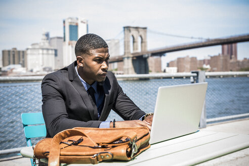 USA, Brooklyn, businessman working with laptop outdoors - GIOF01489