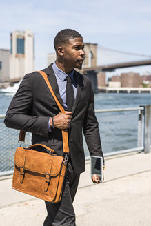 USA, Brooklyn, walking businessman with briefcase and mini tablet - GIOF01492