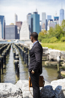 USA, Brooklyn, businessman standing in front of Manhattan skyline - GIOF01498