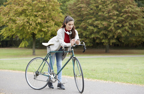 Woman with bicycle in an autumnal park looking at cell phone - FMKF03110