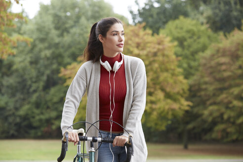 Woman with headphones and bicycle in an autumnal park - FMKF03113