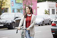 Relaxed woman with headphones and bicycle crossing the street - FMKF03116