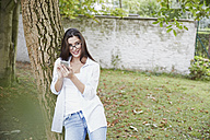 Young woman with smartphone leaning against tree trunk - FMKF03122
