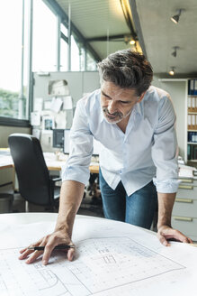 Architect working on ground plan in office - TCF05141