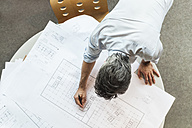 Architect working on ground plan in office - TCF05144