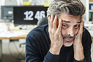 Mature man sitting in office with head in hands - TCF05171