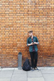 Young skateboarder standing in front of brick wall - BOYF00604