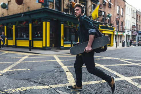 Ireland, Dublin, young man with headphones and skateboard crossing the street - BOYF00613