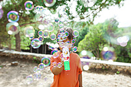 Little boy playing with soap bubble machine - VABF00804