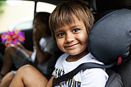 Portrait of smiling little boy sitting on backseat of a car - VABF00816