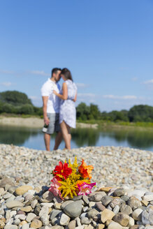 Bunch of flower on pebbles by river, romantic couple standing in background - MABF00406